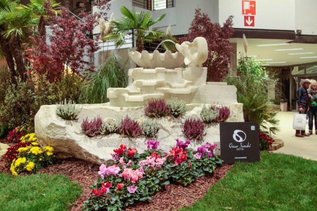 La fontana grezza con delfino, in marmo trani, esposta nella hall del padiglione di Anica a Fiera Cavalli 2015